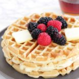 Close up of fluffy waffles with butter and berries