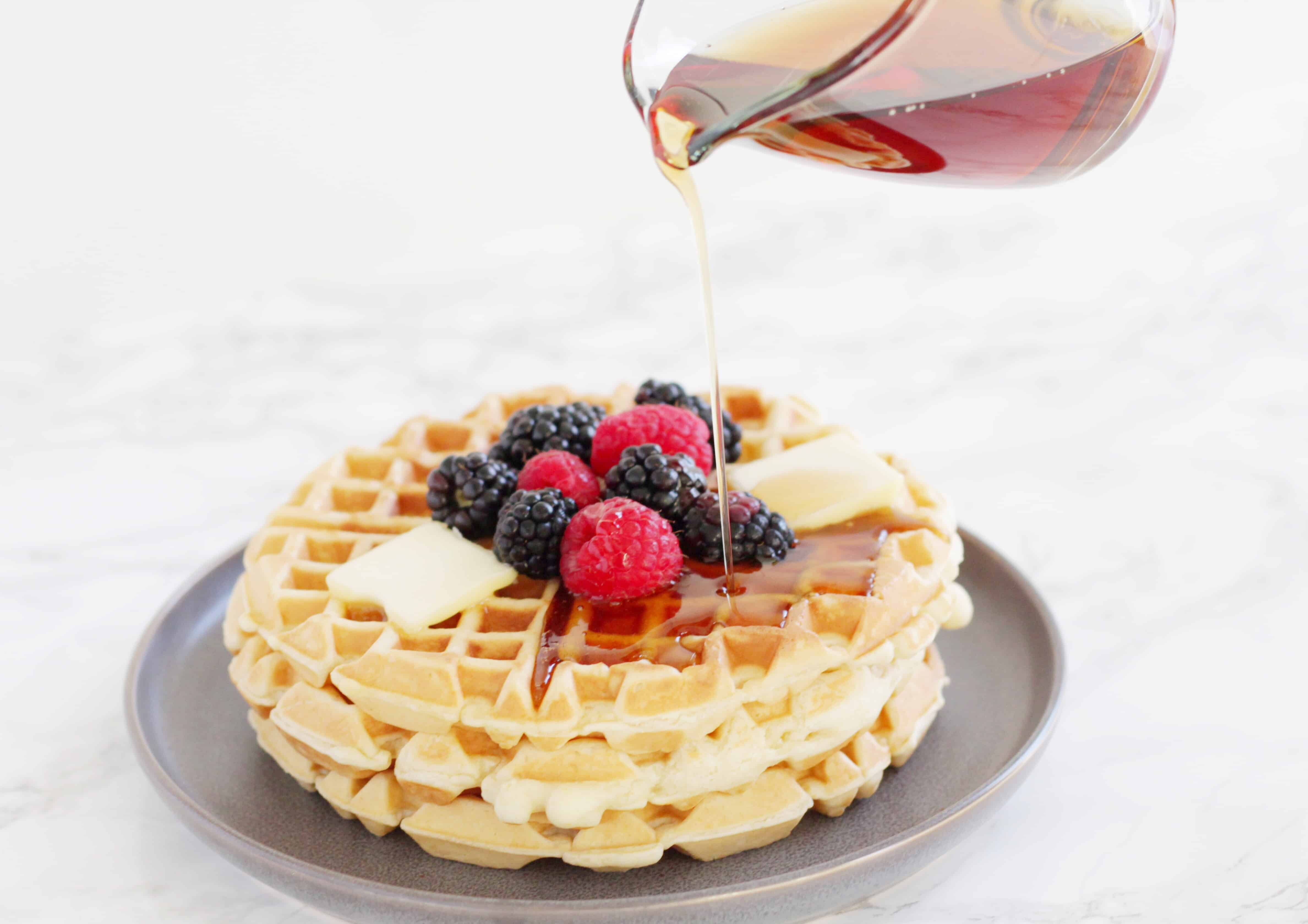 Syrup being poured on fluffy waffles topped with fruit