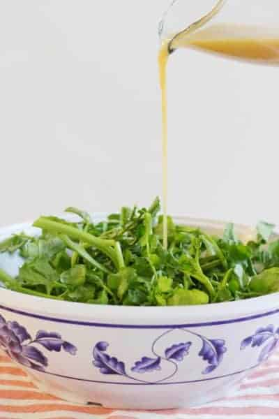 Watercress salad being drizzled with lemon miso dressing