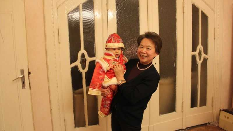 A grandmother holding her grandson in a red Chinese suit
