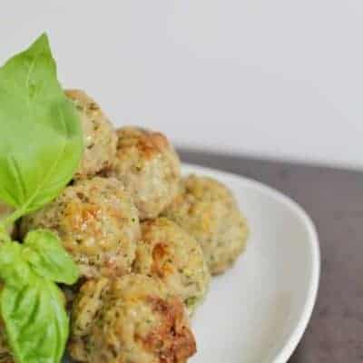 A pile of baked meatballs with some basil