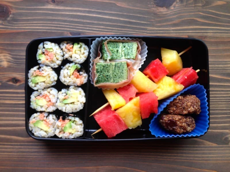 Healthy lunch box with sushi and fruit