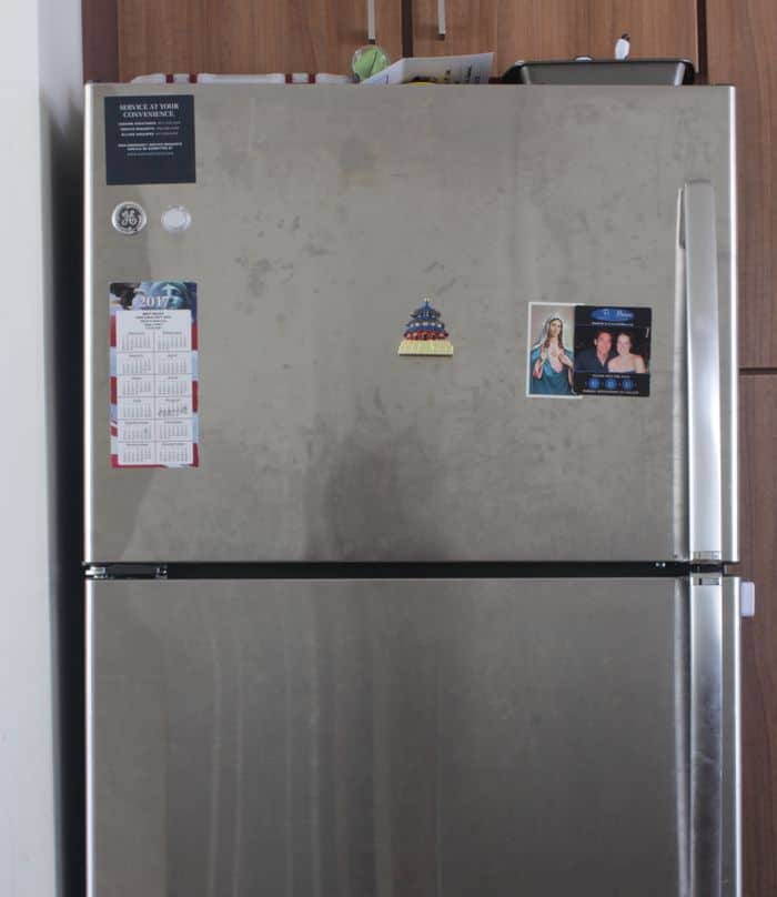 A dirty stainless steel fridge, ready to be cleaned