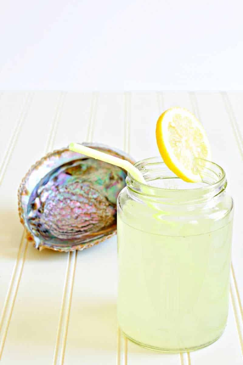 Yellow lemonade in a glass next to a shell