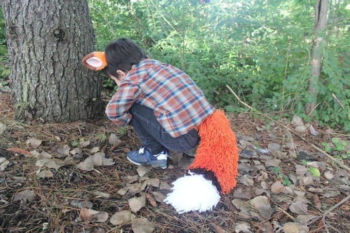 Boy with yarn fox tail in the woods
