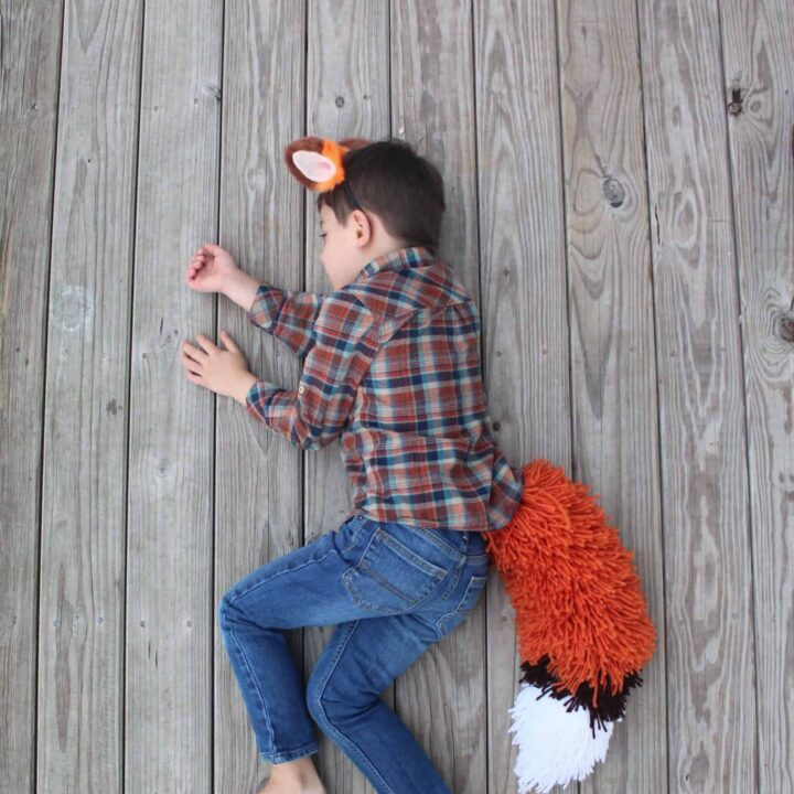 Boy sleeping in his fox tail costume