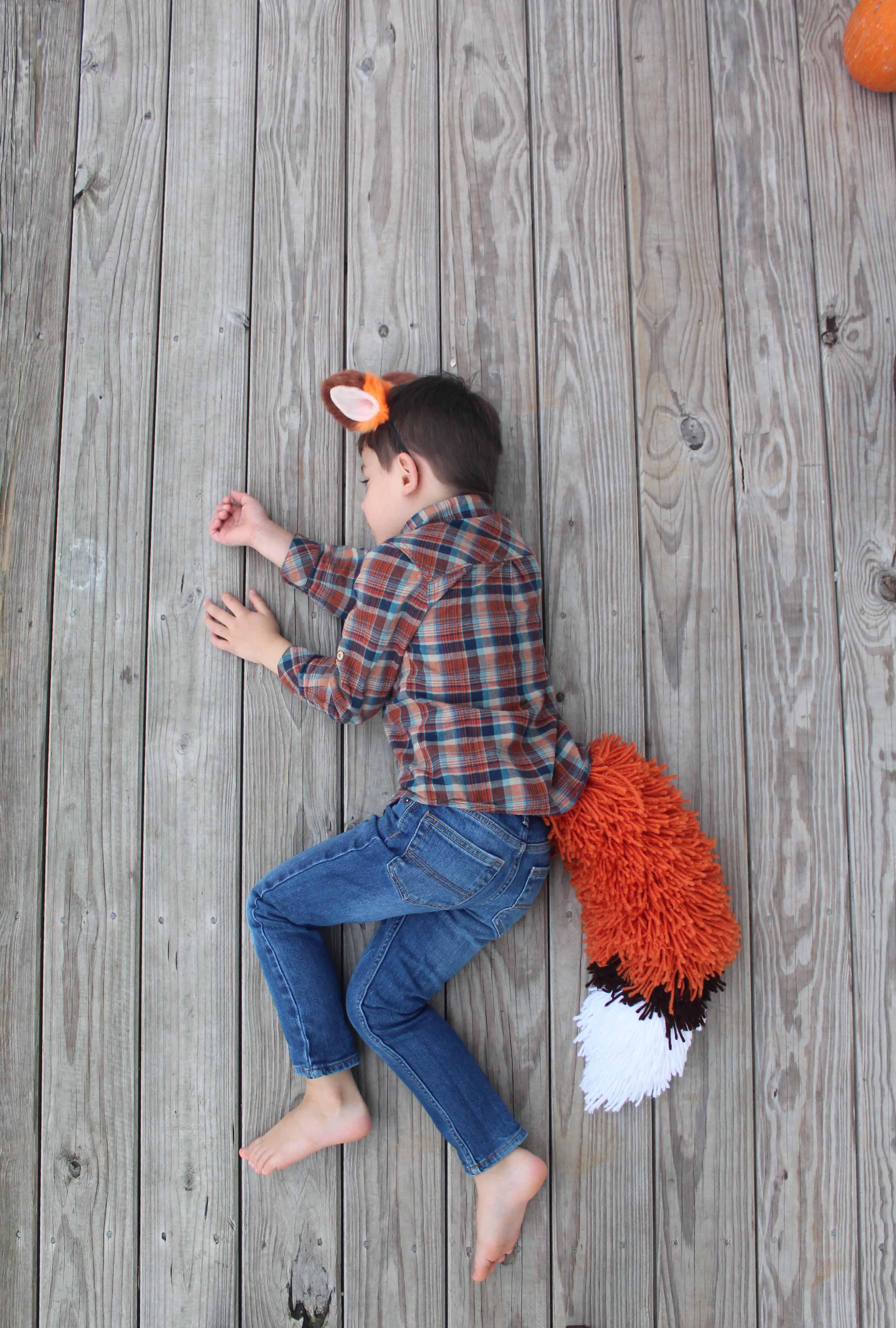 Boy sleeping in his fox tail costume