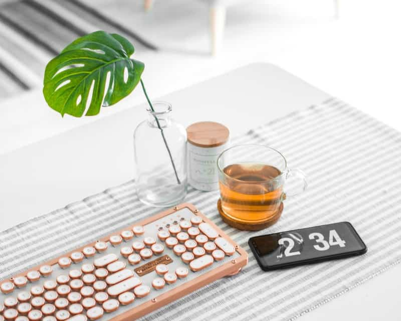 A zen table with keyboard, plants, and tea