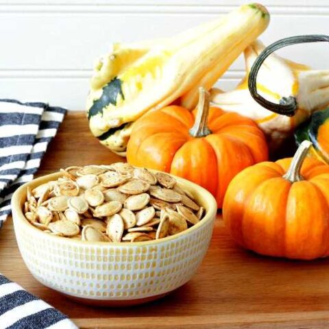 A bowl of pumpkin seeds on a platter