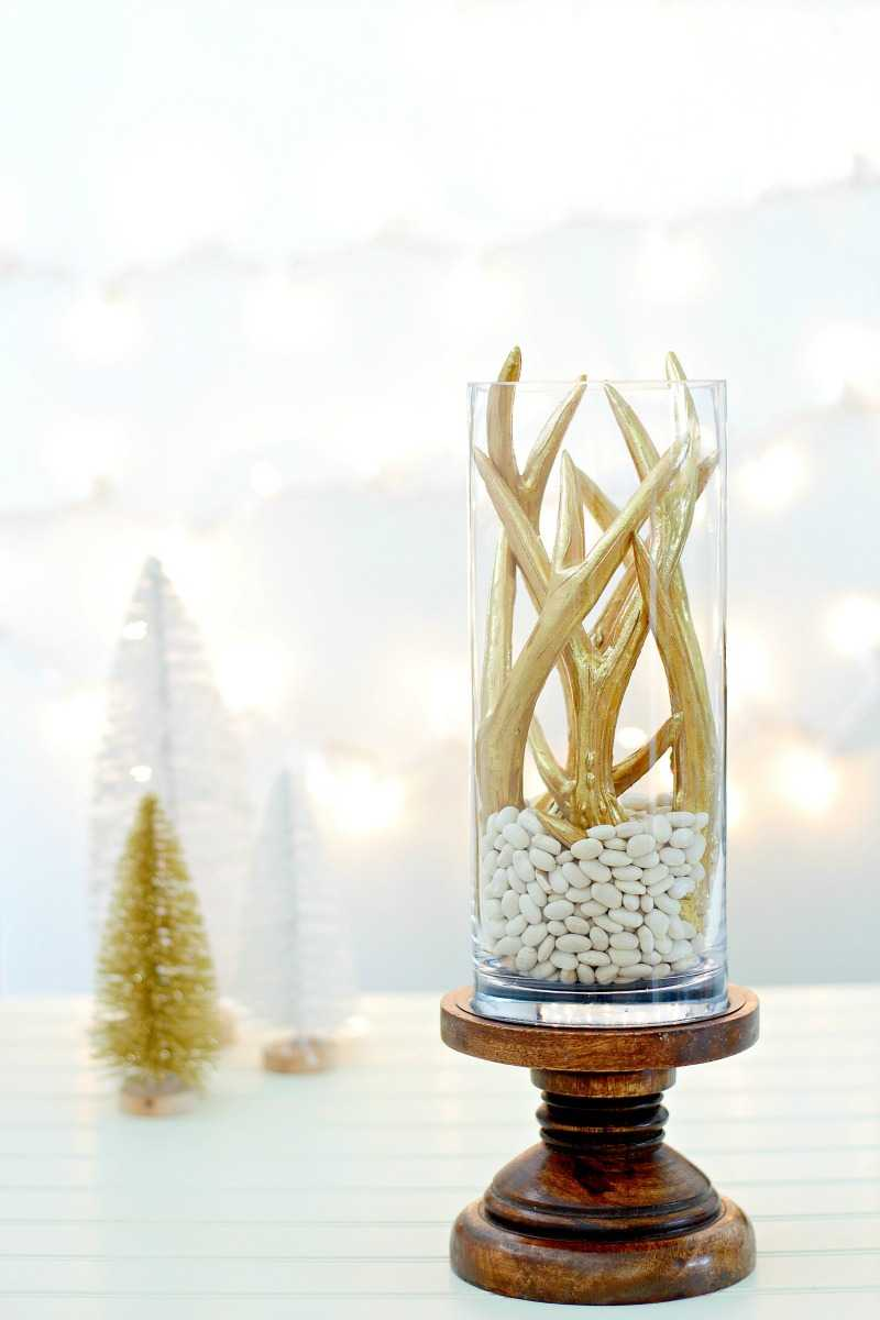 A Christmas centerpiece with white lights behind