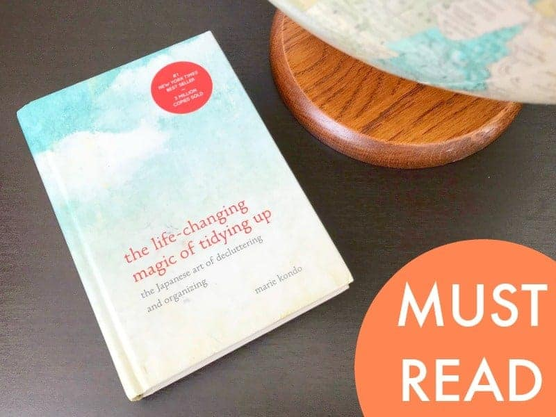 KonMari method book laying next to a globe