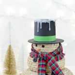 A DIY snowman craft next to small trees