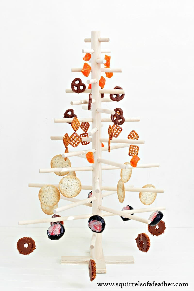 A wooden christmas tree decorated with food.