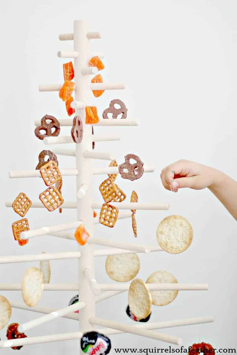 Small hand decorating wooden dowel Christmas tree with edibles.