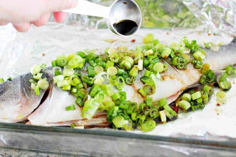 Adding soy sauce to Chinese fish dish