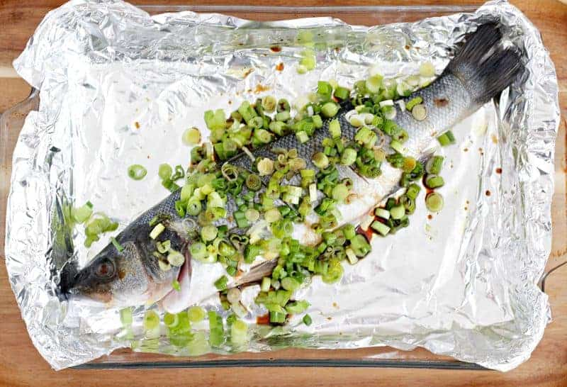 Chinese fish baked in a pan with green onions