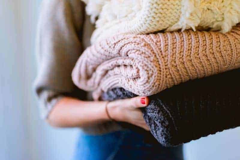 A woman holding KonMari folded sweaters in a neat pile