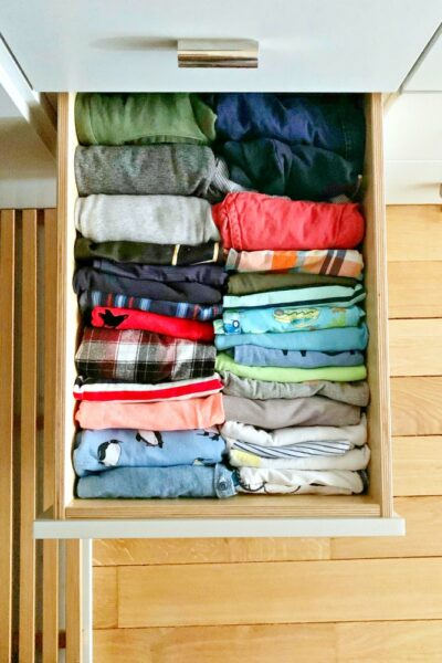 Flat lay view of drawer filled with clothing folded Marie Kondo style