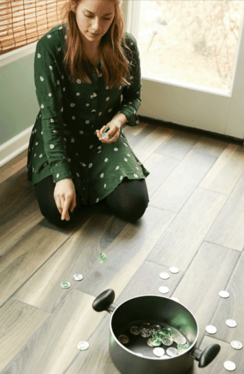 A woman showing kids how to play St. Patrick's Day game
