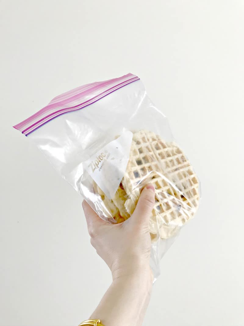 A hand holding frozen waffles in a bag