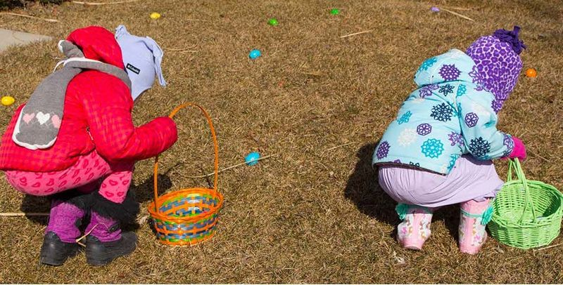 Two children playing Easter game hunting eggs