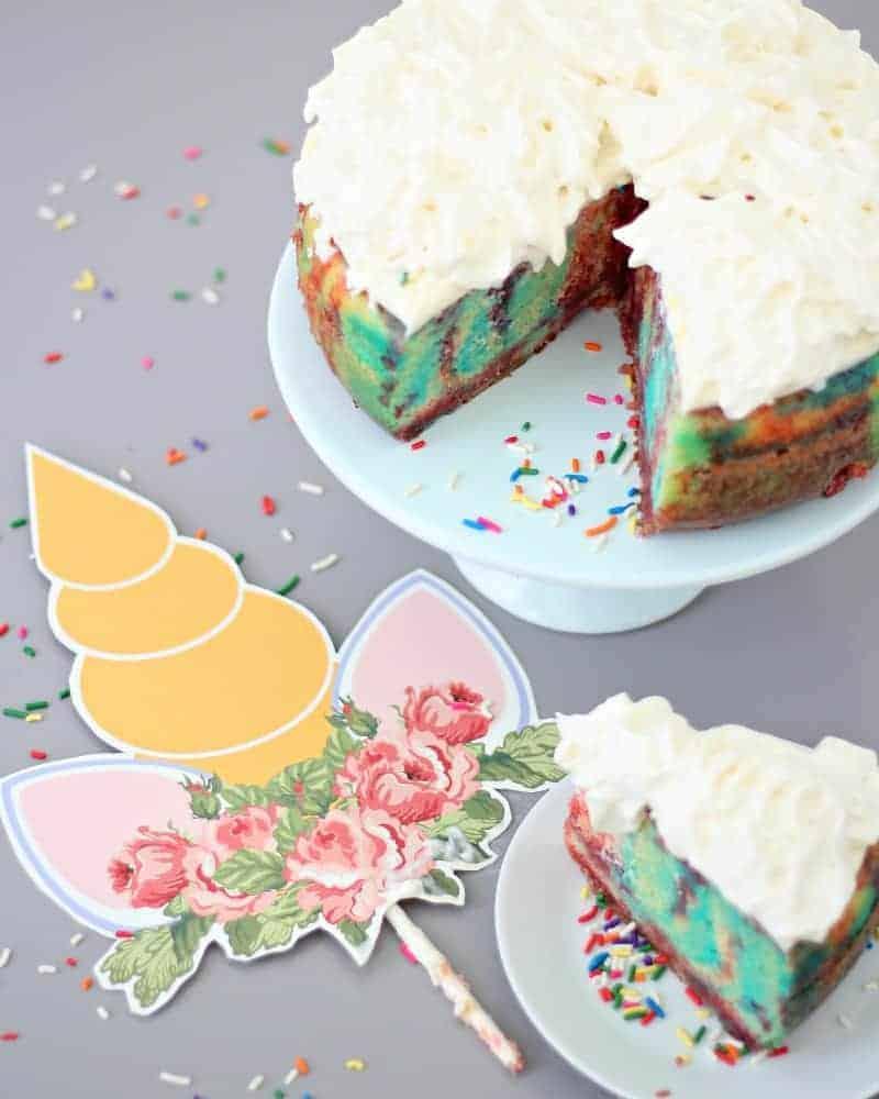 A printable unicorn cake topper next to unicorn cake