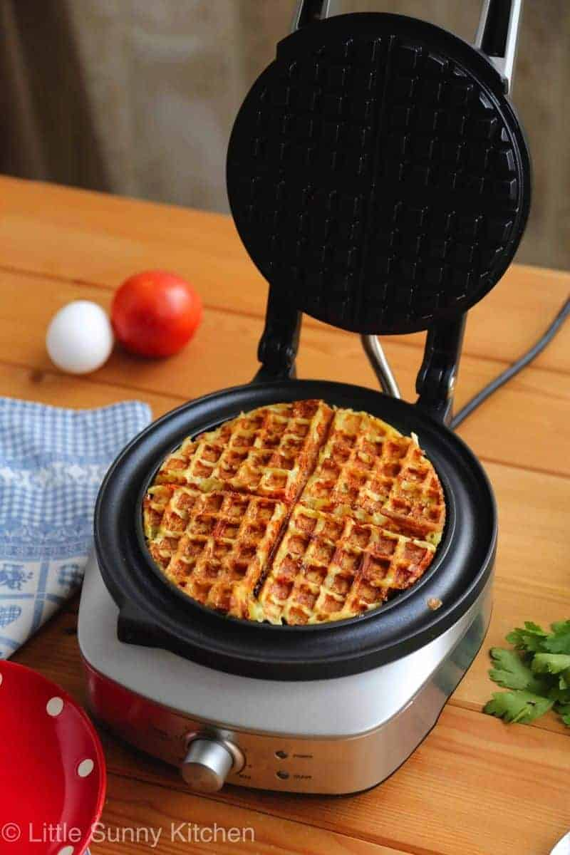 Potatoes and eggs cooking in a waffle iron