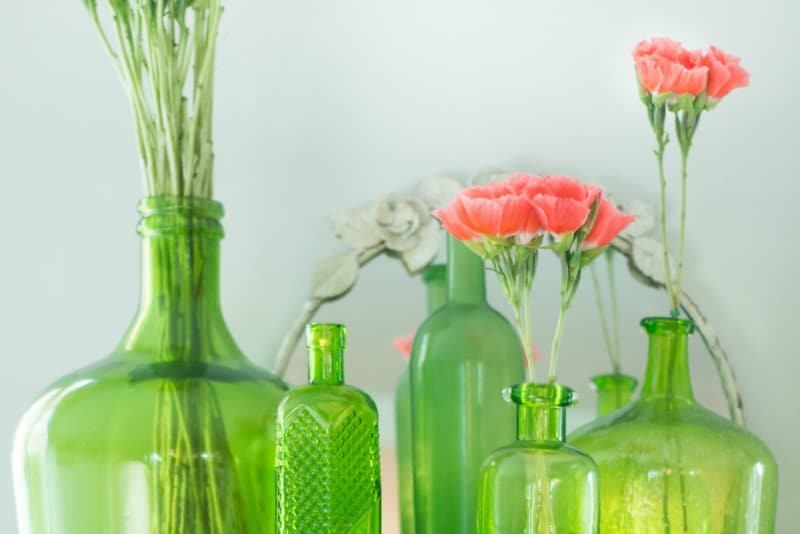 Beautiful green thrift store vases with flowers in them.