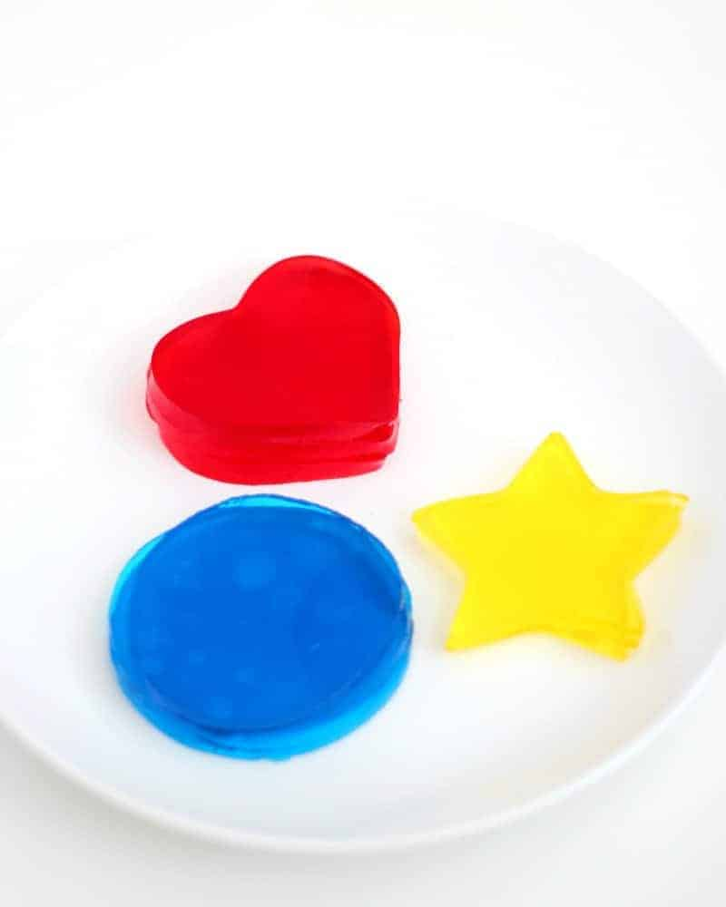 Red, blue, and yellow Jello Jigglers on a plate
