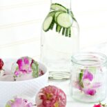 Flowers in ice next to a carafe of cucumber water