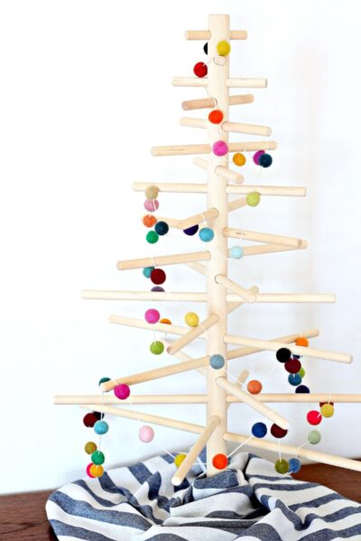 A wooden dowel tree decorated with a colorful felt ball garland