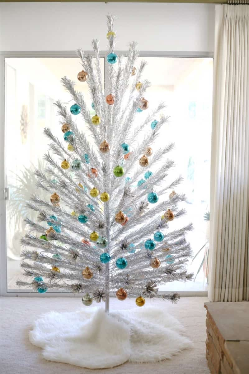 A white aluminum minimalist Christmas tree with colorful ornaments