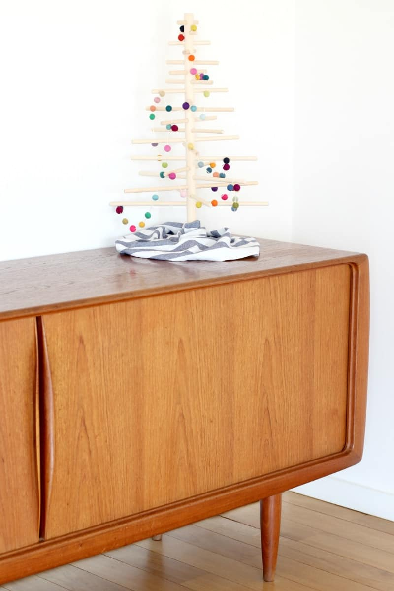A minimlaist Christmas tree on a modern sideboard