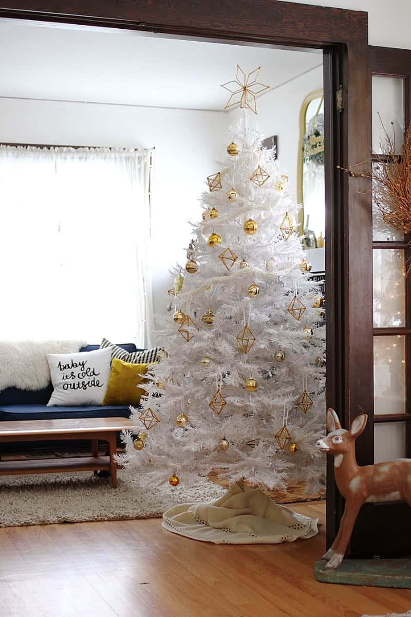 A white minimalist christmas tree with gold ornaments