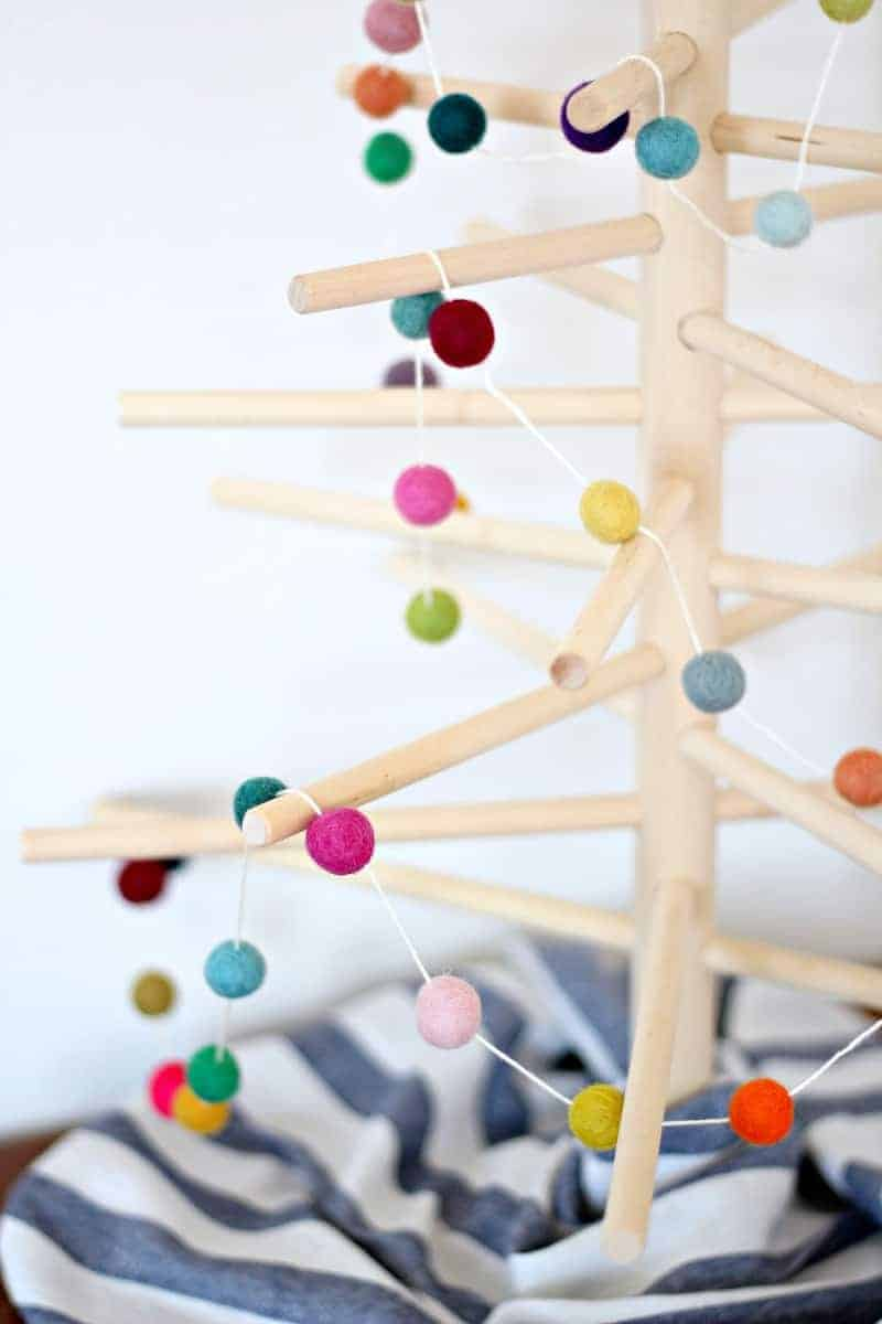 Close up of a felt ball Christmas garland on a wood tree