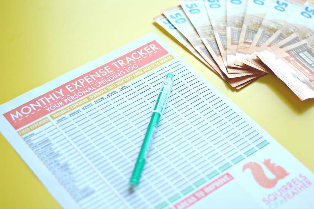 Close up of a free printable monthly expense tracker on a yellow table