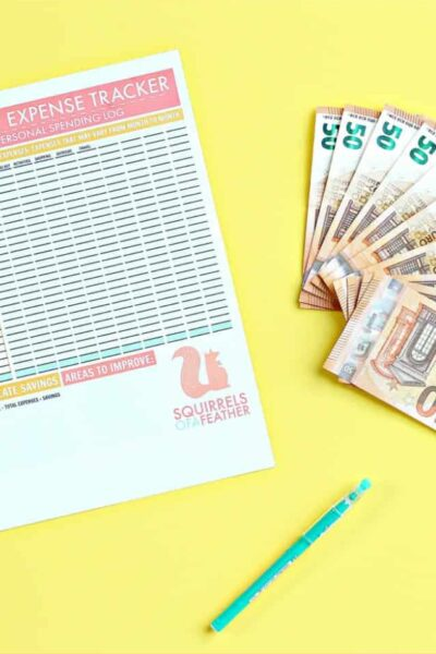 A monthly expense tracking printable laying next to money and a pen