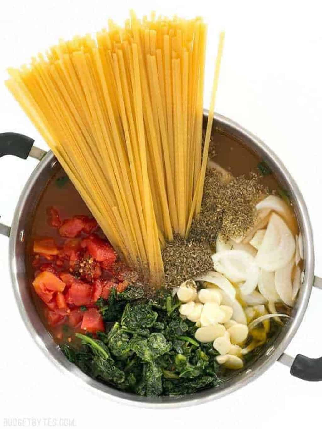 A pot of pasta, veggies and liquid being cooked in one pot