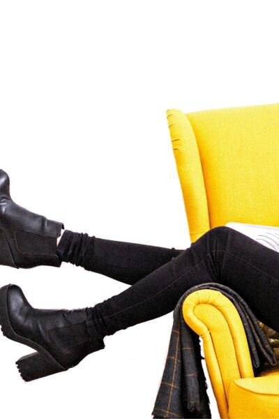A woman in black pants making money from home on a yellow couch