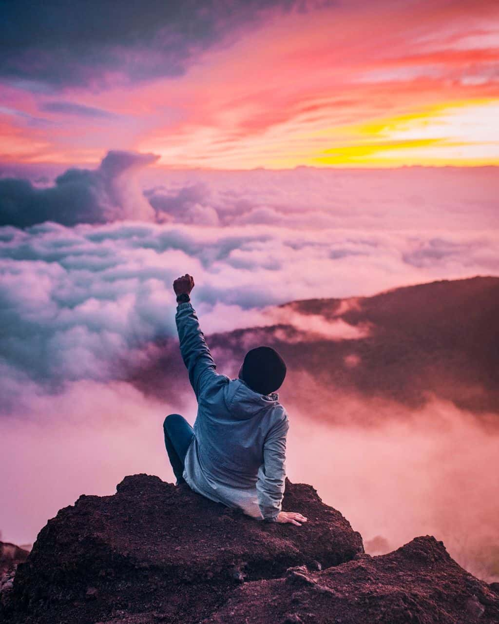 A man raising his fist to the sunrise because he is debt free