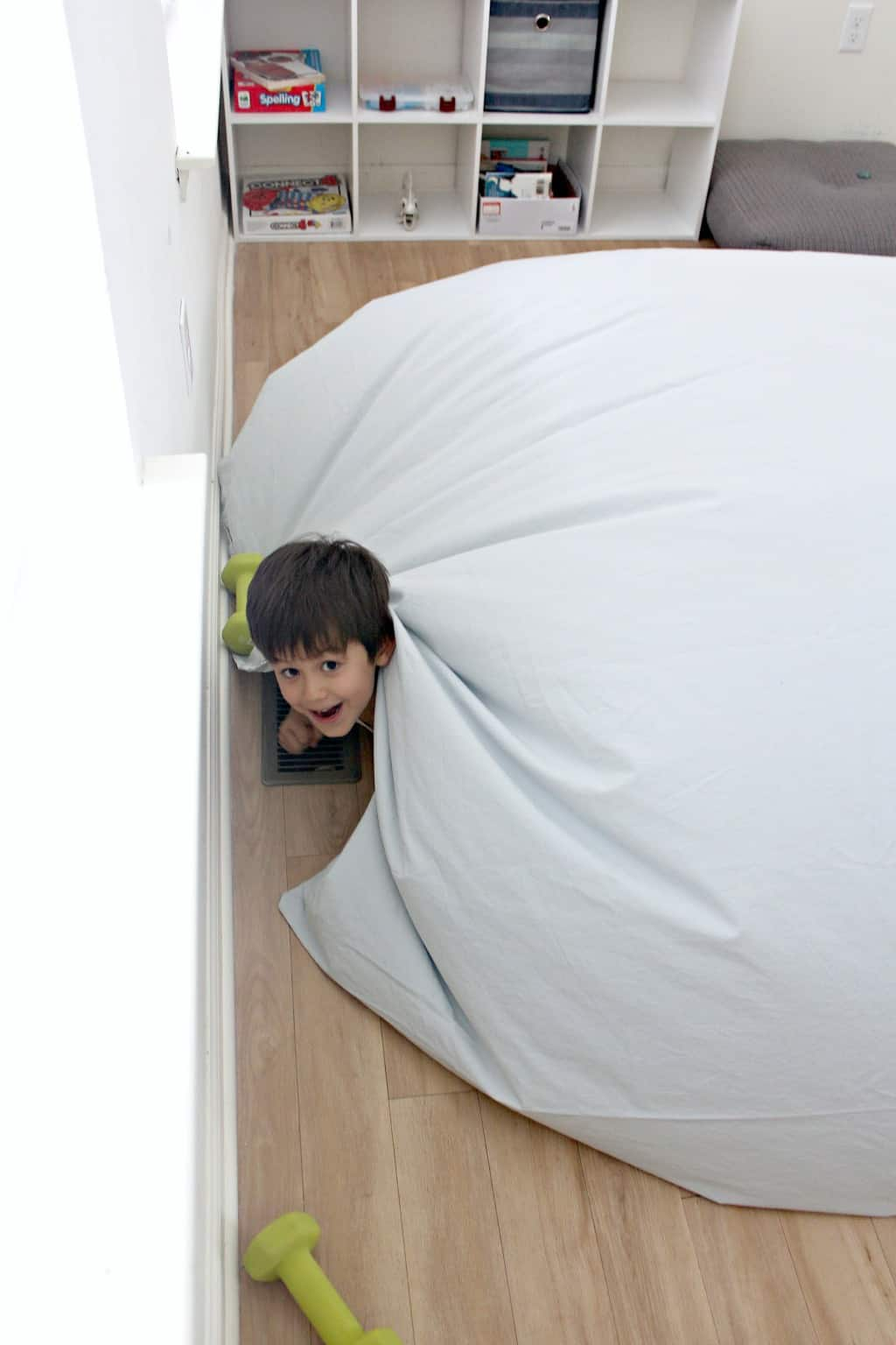A boy peeking out from under an air fort.