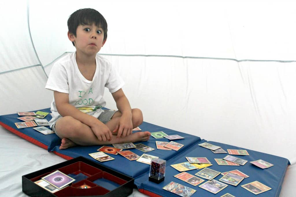 A boy playing with cards inside an air tent.