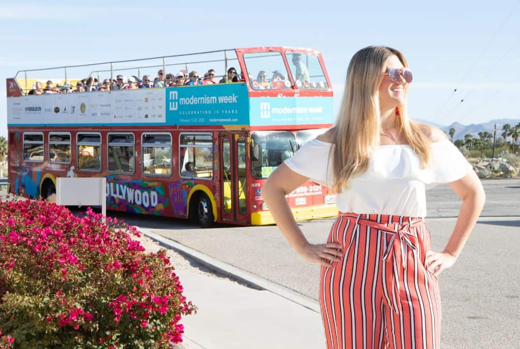 A travel blogger posing in front of a bus