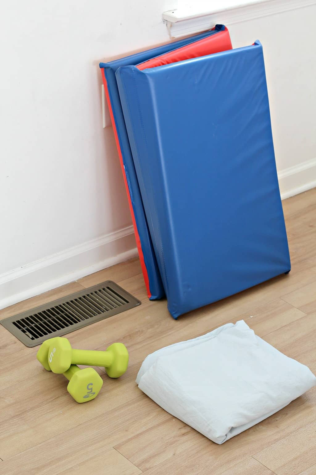 Supplies for making a DIY air fort tent at home, including sheet and play mat.