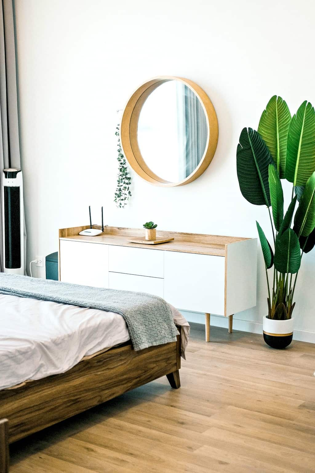 A decluttered bedroom with round mirror and plants