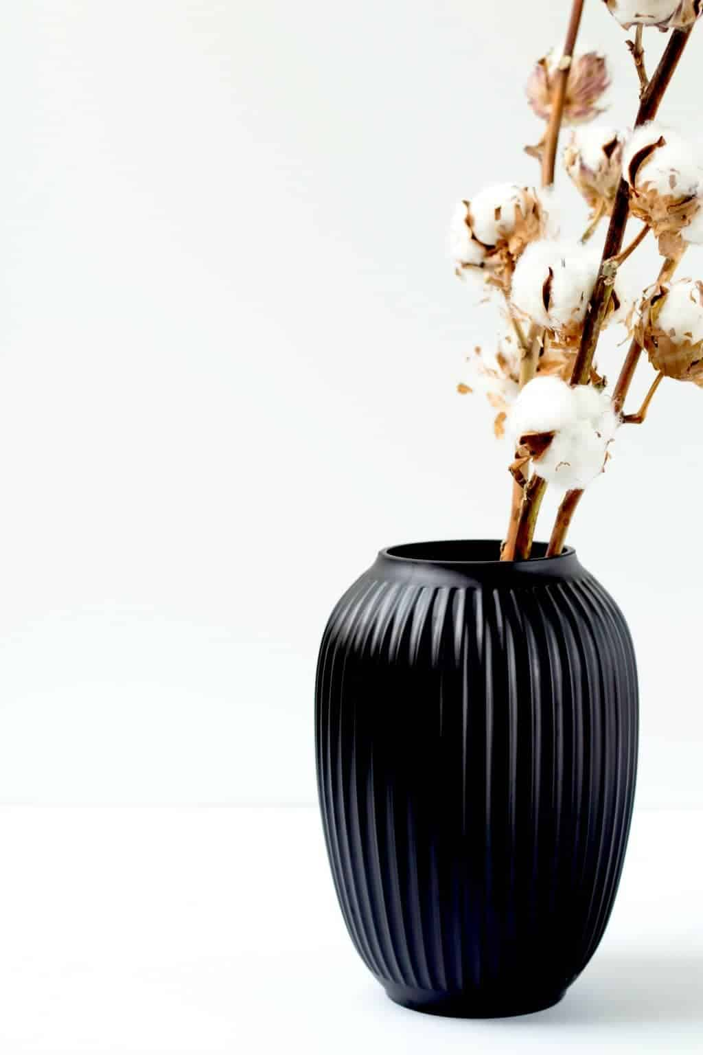 A minimalist black vase with cotton inside of it
