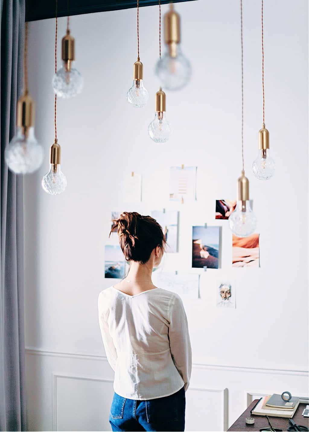 A woman looking at a vision board ideas wall