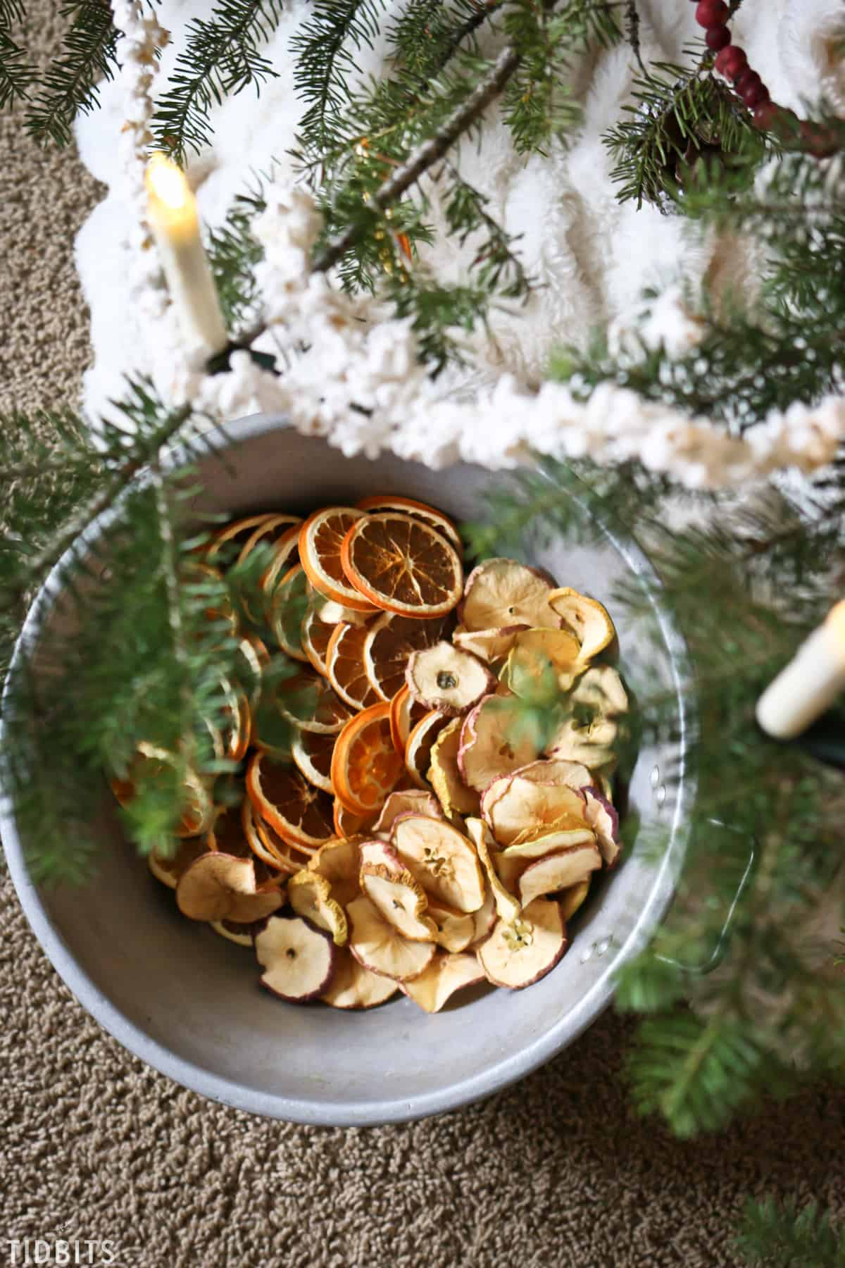A bowl of natural orange and apple decorations being hung on a Christmas tree.