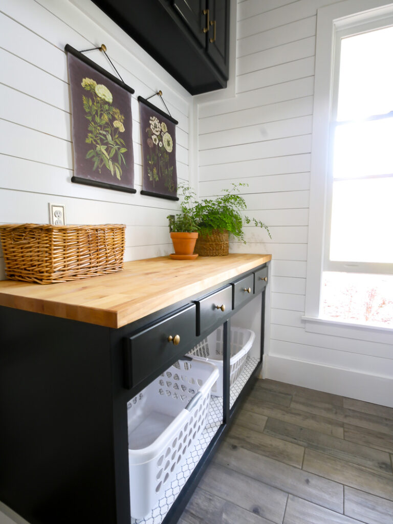 A folding table in a laundry room with laundry basket storage underneath