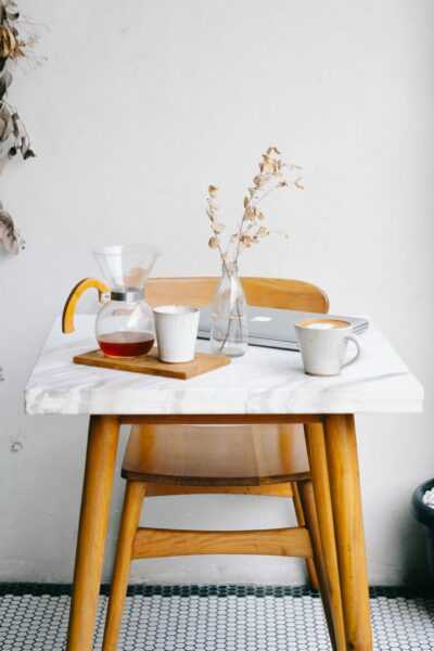 A miniimalist table with pour over coffee and a laptop on top